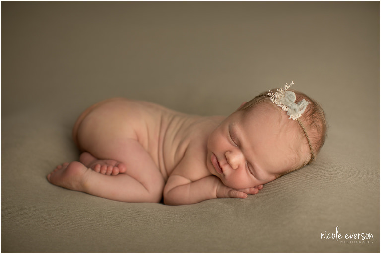 new baby photographed on a dark sage blanket with a beautiful delicate bow in her hair