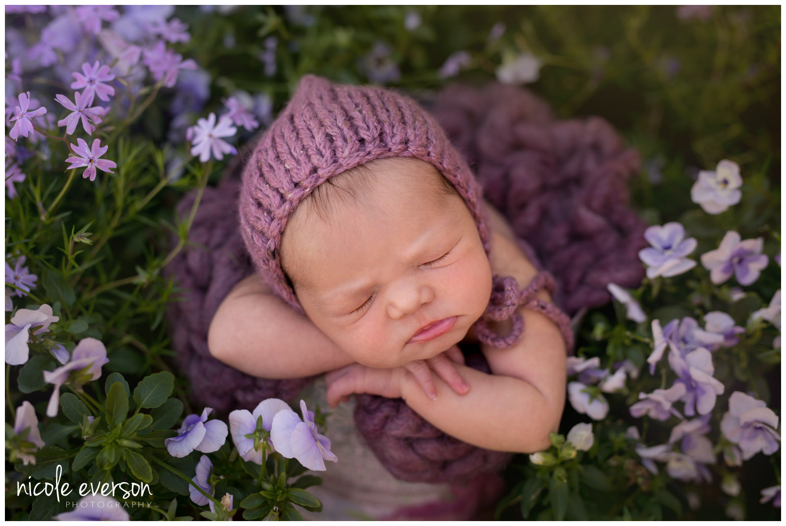 newborn baby girl photographed outside Crestview Florida surrounded by purple spring flowers