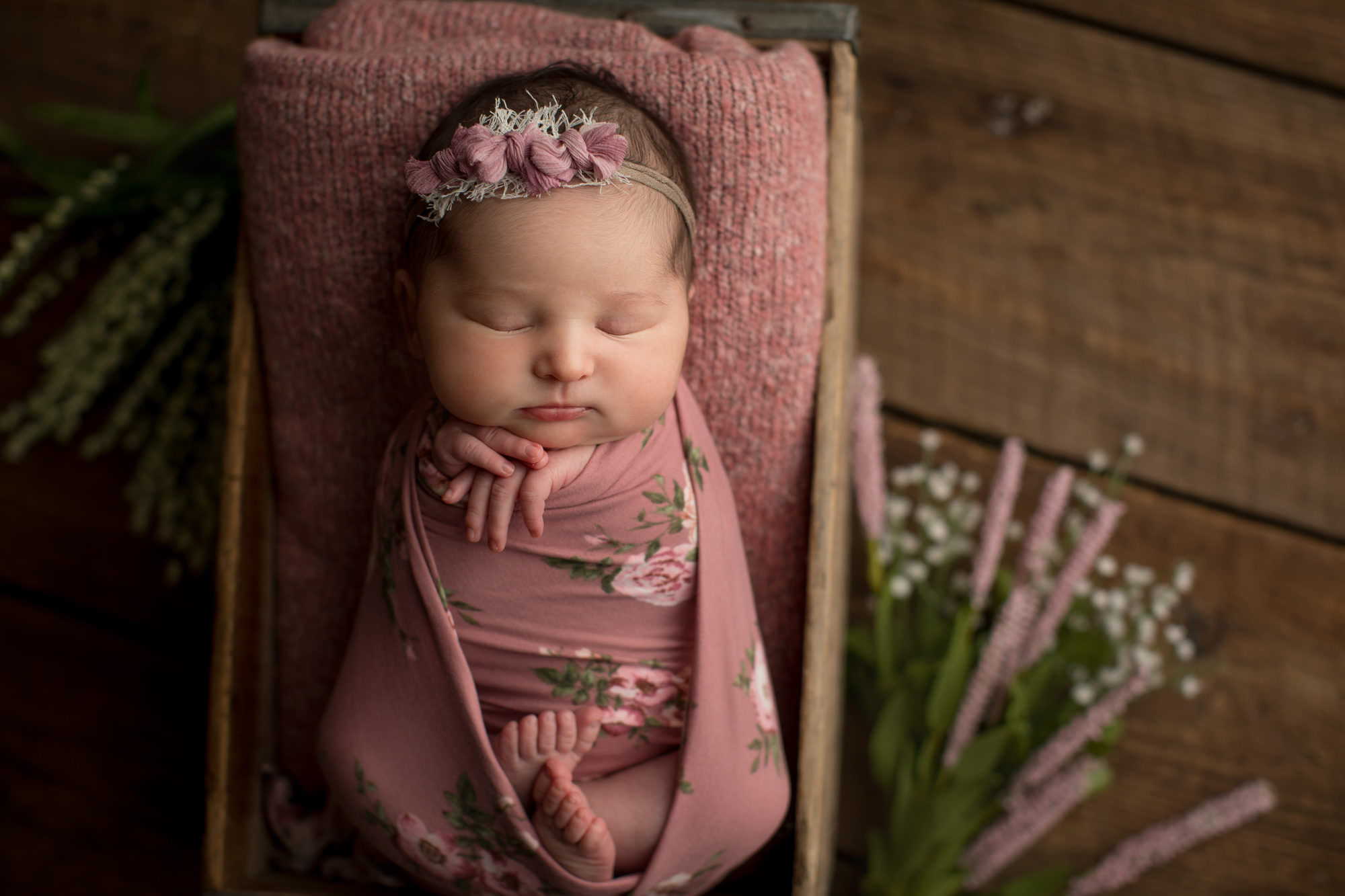 newborn baby girl wrapped in a pink floral wrap