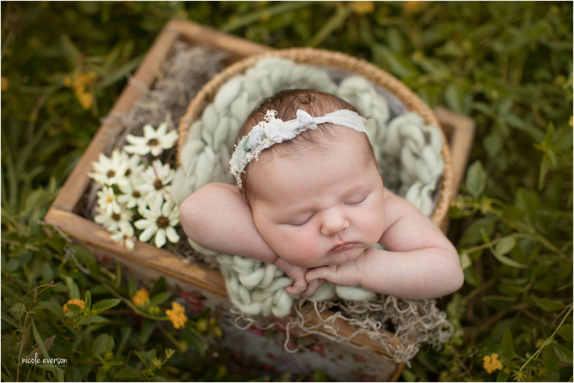 newborn photographed outside in flowers