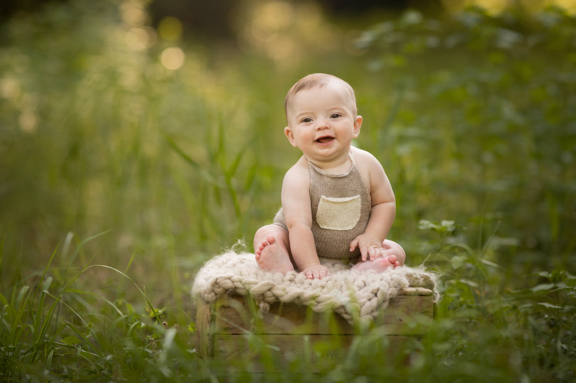 photo of a happy baby boy laughing in a field on 30a