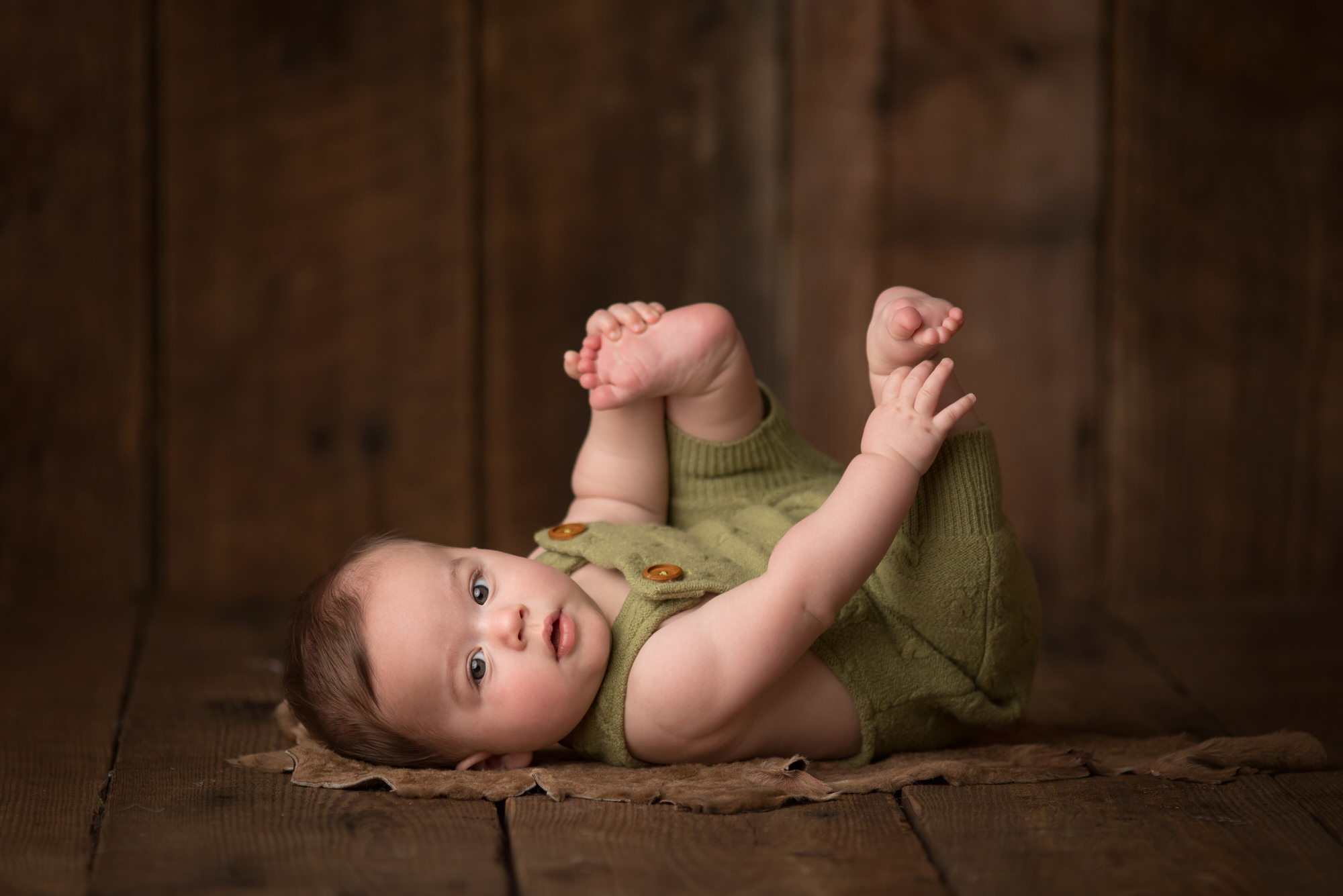 baby boy photographed on dark barn wood