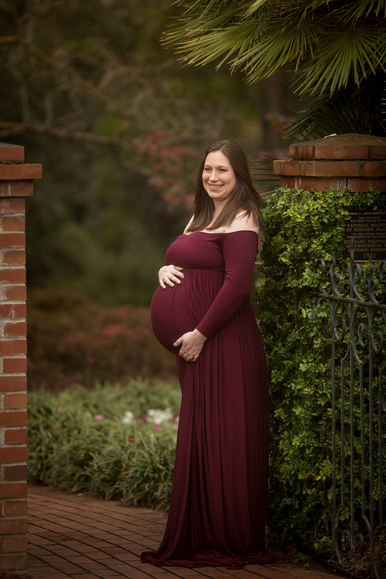 photo of a pregnant woman in Rosemary FL gardens in a plum maternity gown