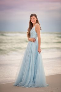 senior photographed in prom dress on the beach in seaside